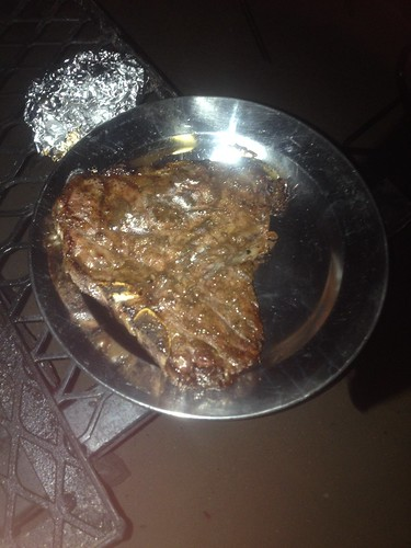 T-bone steak that barely fits on the plate