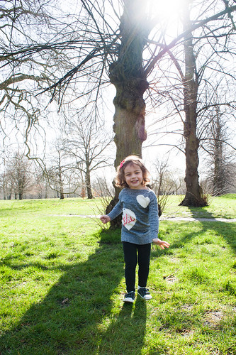 Little girl in a London Park in front of a tree smiling