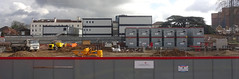 A panoramic view of a building site with grey hoardings in the foreground and portacabins beyond.