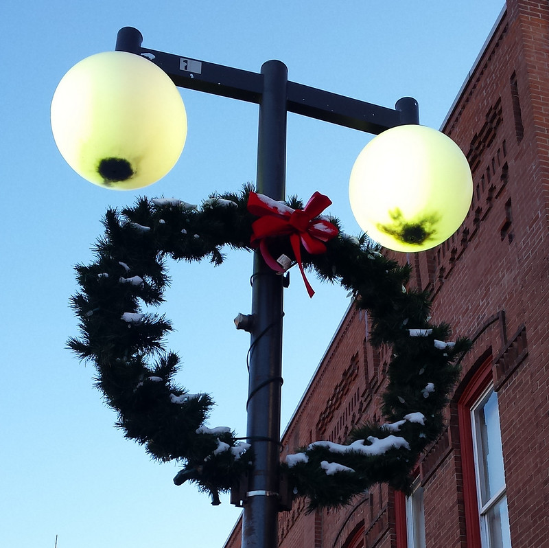 two light bulbs with dead bugs that look like eyes above a large narrow wreath that looks like an open mouth