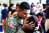 A deploying Soldier kisses a loved one as he prepares to depart on a 12-month mission to Africa in support of Operation Freedom's Sentinel. The farewells were shared by thousands during a deployment ceremony, April 10, at a hangar in Fort Lauderdale, Fla.