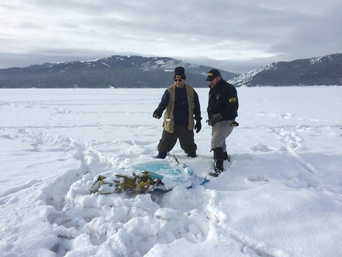Air safety investigators Howard Plagens and Jackie Vanover examine a piece of aircraft structure from the Jan. 4 crash of an Aerostar SA Yak 52 in Palisades Reservoir, Idaho