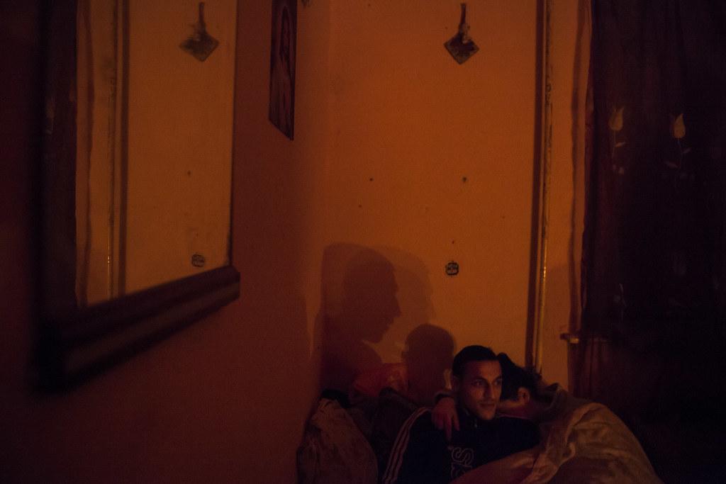 Terike beteg fia és párja a szoba egyik sarkában várja, hogy elcsendesedjenek a kisebbek is. Terike korábban szociális gondozóként dolgozott, most nincs munkája, huszonéves, rákbeteg nagyfiát istápolja, és próbálja rendben tartani a népes családot. Tizenketten élnek a házban, ahol vezetékes víz sincs amióta 3-4 éve volt egy csőtörés, és nem tudták megcsináltatni. | Fotó: Magócsi Márton