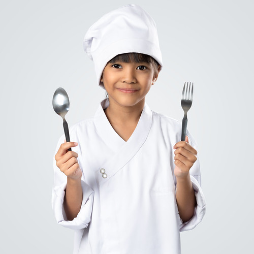 Happy little chef holding a spoon and fork