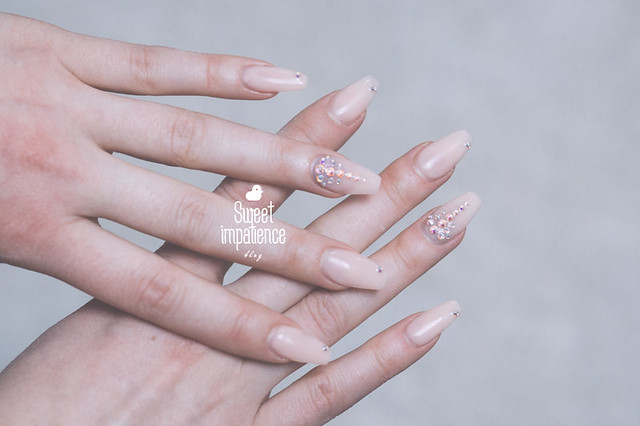 Nude baby pink gel nails with different size Swarovskis in Crystal AB.