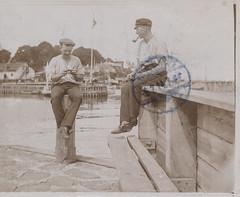 Two men smoking on a pier