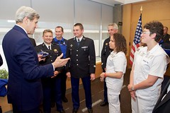 Holding a model helicopter, U.S. Secretary of State John Kerry thanks French nurses and a helicopter flight crew on May 2, 2016, as he visited the U.S. Mission in Geneva, Switzerland, and thanked the first responders who treated him after he broke his leg in a biking accident in nearby France on May 31, 2015. [State Department photo/ Public Domain]