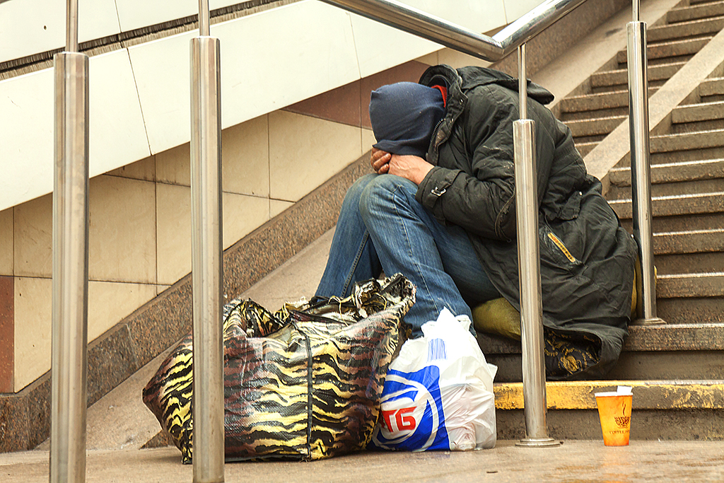 Man with head down, sitting on subway entrance step--KIev