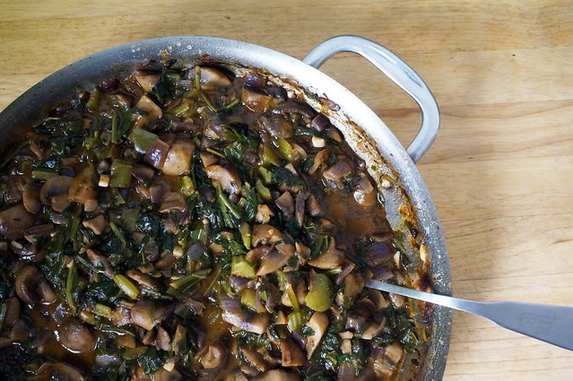 A pan of smothered mushrooms and spinach, dark green vegetables jostling against rich brown mushrooms. A stainless steel spoon, half-submerged, hangs over the pan's edge.