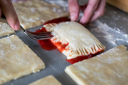 crimping the edges of the pie with a fork
