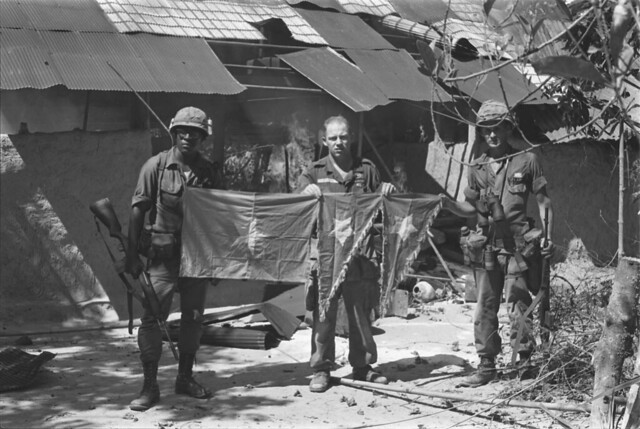 Hậu Nghĩa 1966 - U.S. soldiers with captured Vietcong flag.