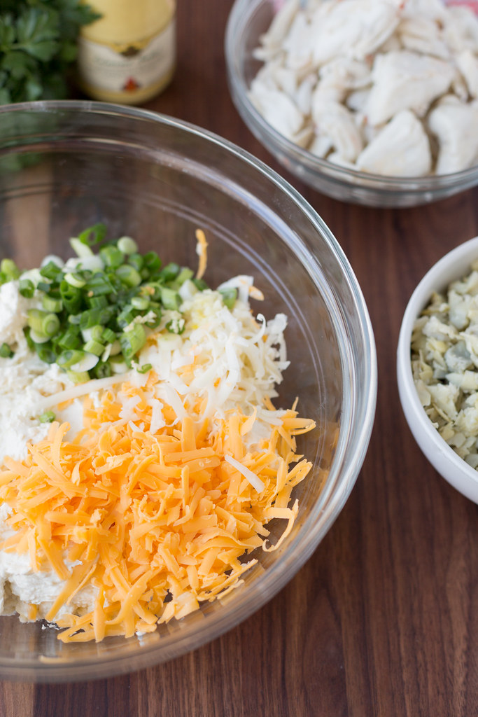 crab dip ingredients in bowl with cheddar cheese