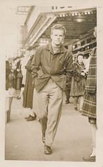 Young man walks down a sidewalk