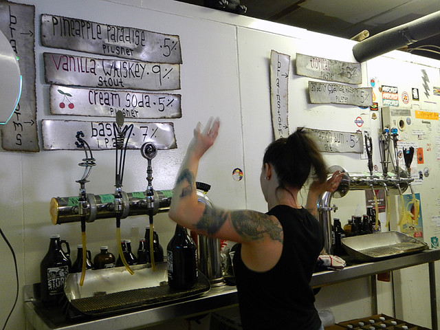 A bartender dances while she waits for a growler to fill at Storm Brewing in Vancouver