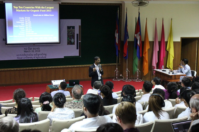 Crowd of students listening to Ramu Govindasamy speak with PowerPoint slides behind him about countries with top organic markets. IMG_9142