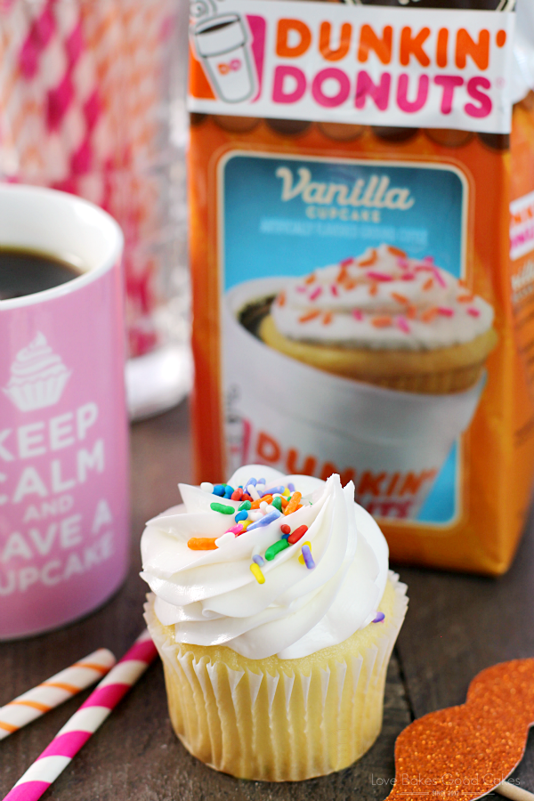 Bakery-Style Vanilla Cupcakes with white frosting and rainbow sprinkles with a bag of Dunkin Donut coffee.
