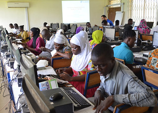 men and women working on computers in classroom with projector and teacher in background