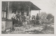 Grungy photo of a group of men sitting on a porch
