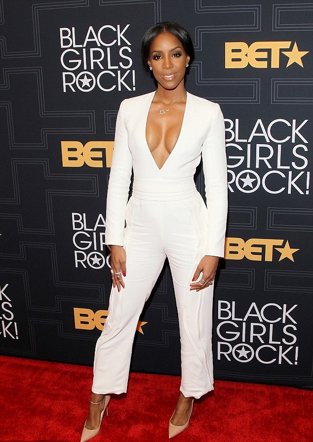 plunging-neckline-white-jumpsuit-nude-heeds-star-pendant-necklace-series-of-rings-on-her-hand