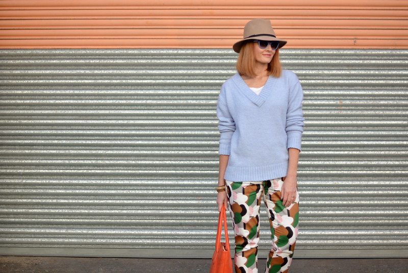Spring style: Bold patterned pants, pale knit, orange tote, camel fedora | Not Dressed As Lamb