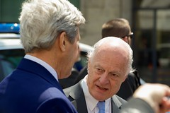 U.S. Secretary of State John Kerry listens as United Nations Special Envoy for Syria Staffan de Mistura addresses reporters gathered outside the Hotel President Wilson in Geneva, Switzerland, on May 2, 2016, amid a series of meetings focused on the cessation of hostilities in Syria. [State Department photo/ Public Domain]