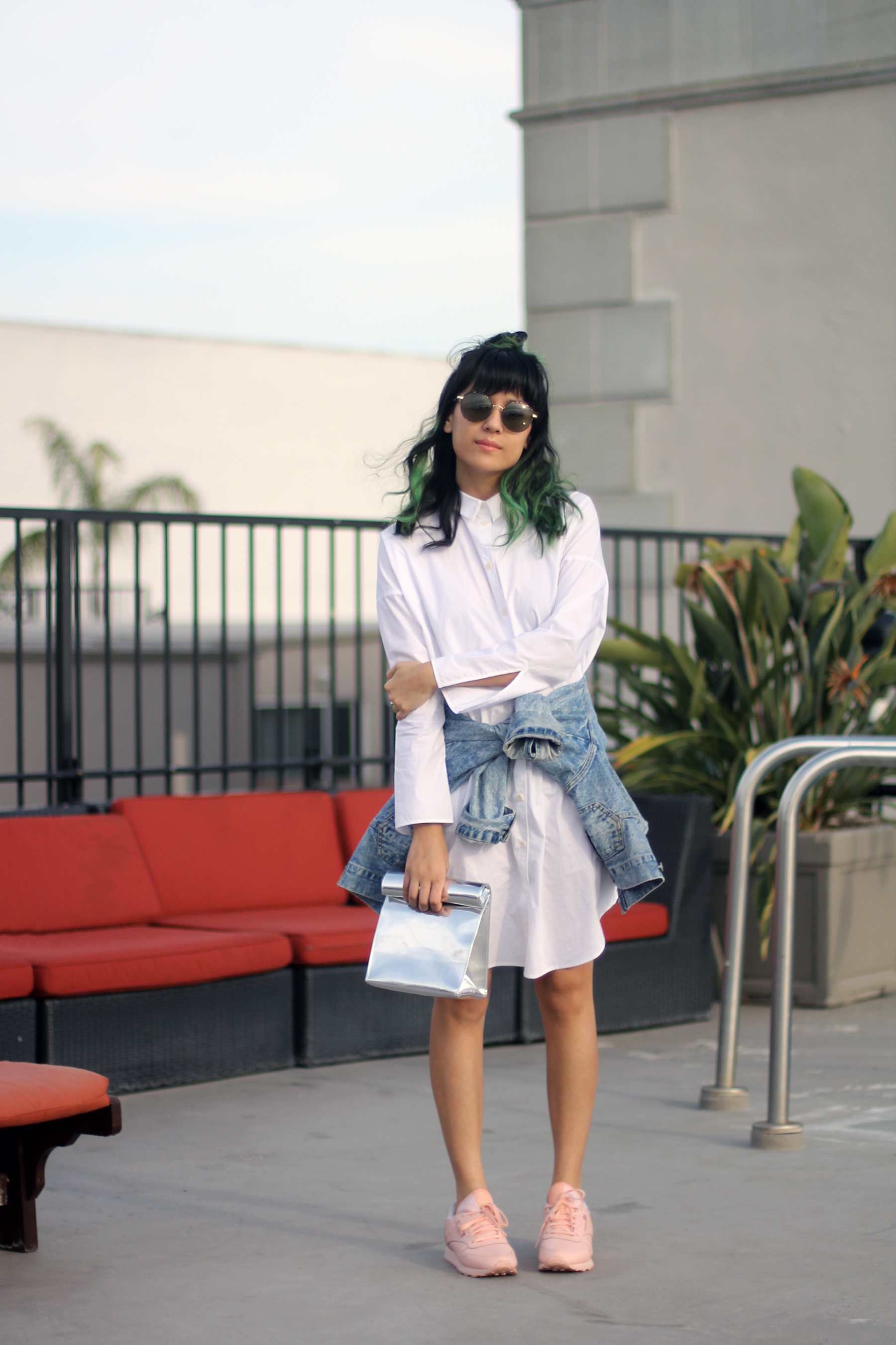 Acne Studios Poplin Shirt Dress, Pink Reebok tennis shoes, green hair, New Classics Studios SMK metallic foldover clutch, The Row sunglasses