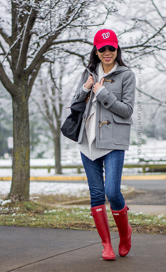 red baseball cap, gray toggle coat, sherap lined open sweater/sweatshirt, jeans, red rain boots