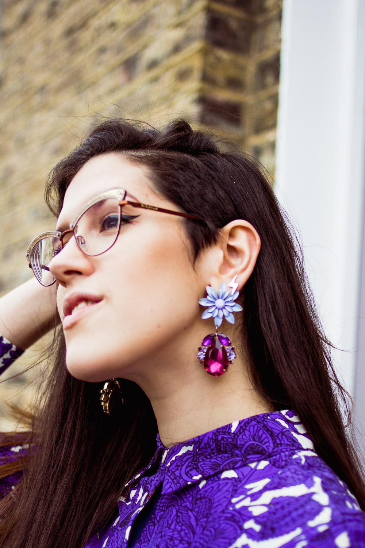 purple drop earrings and a purple print shirt