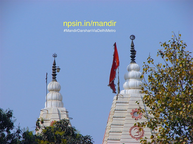 Trishul of Lord Shiv, Omkaar a holy Hindu symbol and sinduri red flag hosted on the top of white shikhar. A beautiful greenery frame this picture very well.