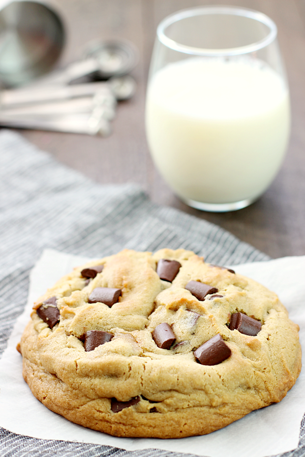 Giant Peanut Butter Cookie with Chocolate Chunks close up with a glass of milk.