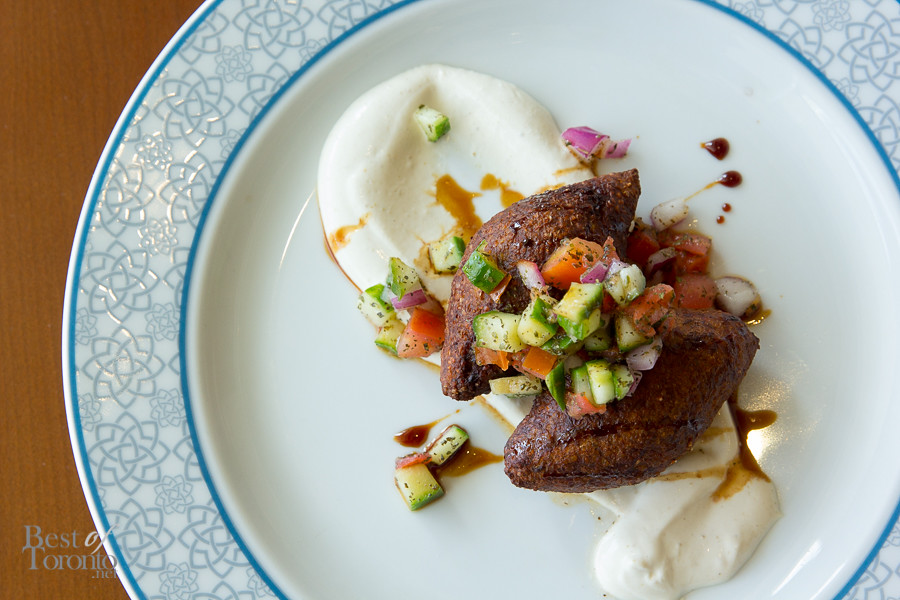 Lamb kibbeh with toasted pine nuts, golden raisins, citrus tahini, and shirazi salsa