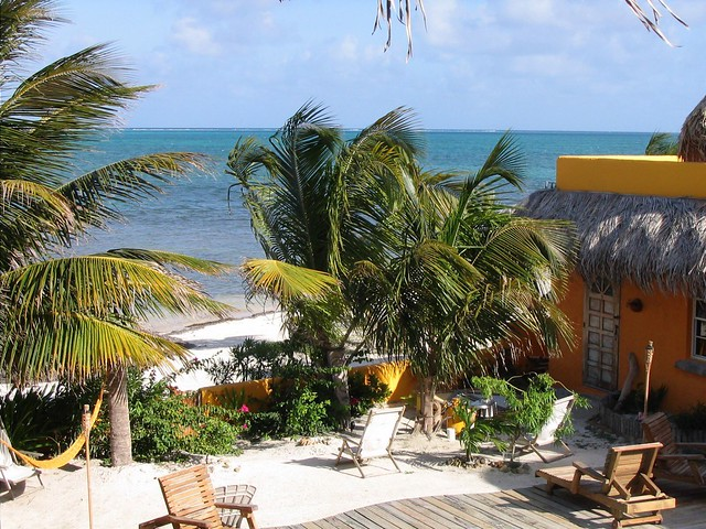 Best vacation spots for families: this is a sandy beach in Belize with small palm trees for shade and white soft sand