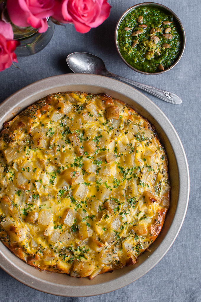 Frittata served as an appetizer or main is the BEST brunch item. Easy to make ahead so you can sip a mimosa or some caffeine with friends. This one--with lots of springy potatoes and leeks--is also decked out with a quick vegan parsley pesto!
