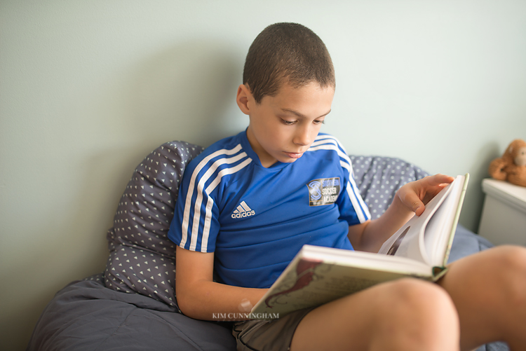 boy reading book on bed 01-750