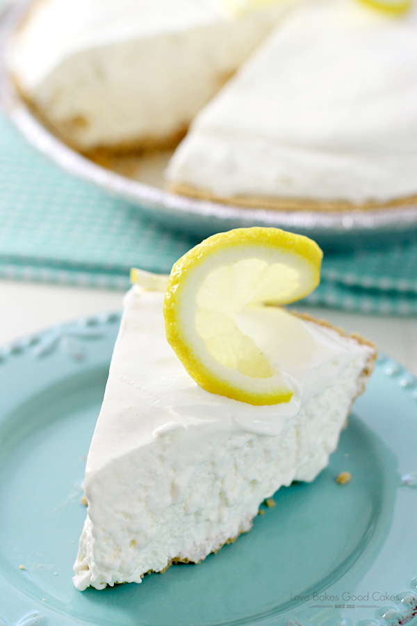 Frozen Lemonade Pie on a blue plate with a slice of lemon.