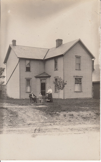 RPPC_father sitting in his rocking chair, mother and daughter standing next to theirs, Lore City, Ohio
