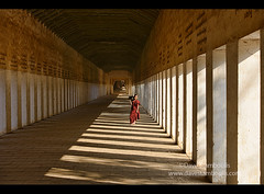 A young monk rwalks through the entrance corridor to Shwezigon Paya, Bagan, Myanmar