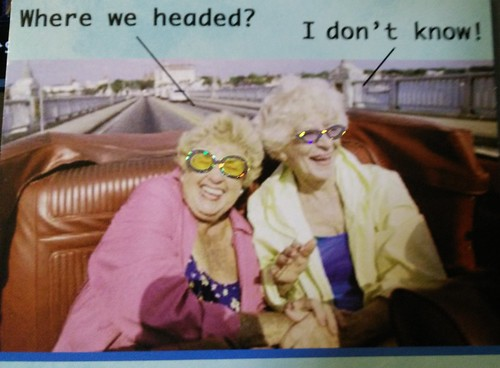 birthday card front showing two old ladies in a red car with shiny sunglasses and laughing. One asks Where we headed? and the other says I don't know!
