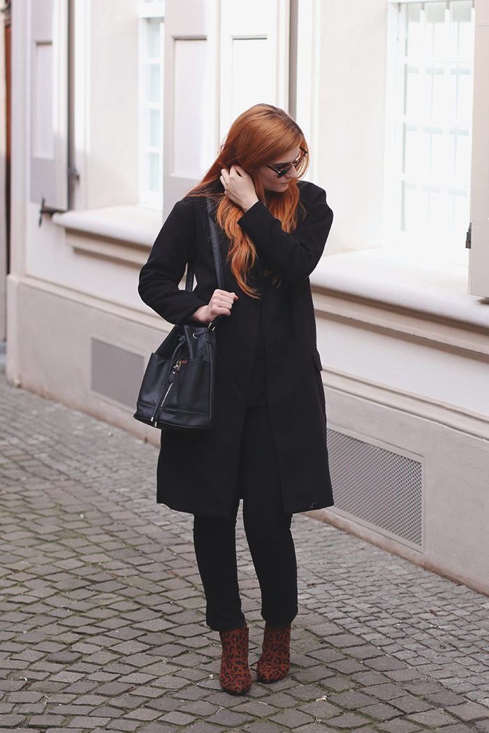 All black with leopard print boots and oversized coat