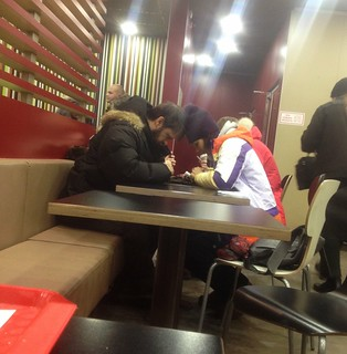 Romance in the air with faces buried in phones at McDonalds