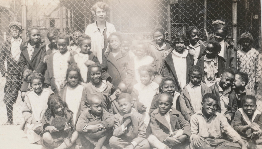 White woman poses with a group of African American children