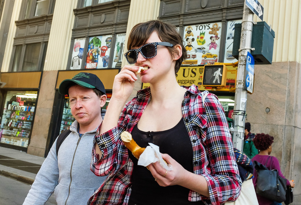 New York City Street Scenes - Young Woman in Sunglasses Eating a Pretzel