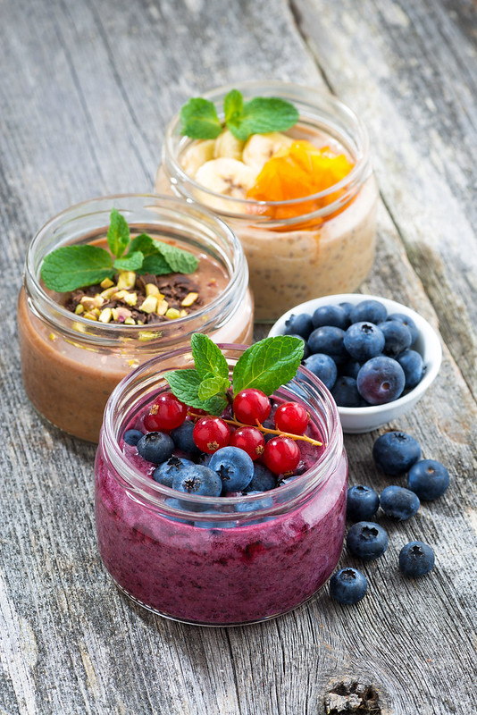 assortment breakfast with fresh berries, fruit and chocolate in glass jars