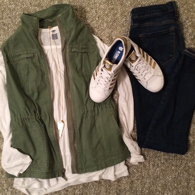 olive vest + white top + skinny jeans + gold necklace + white/gold sneakers
