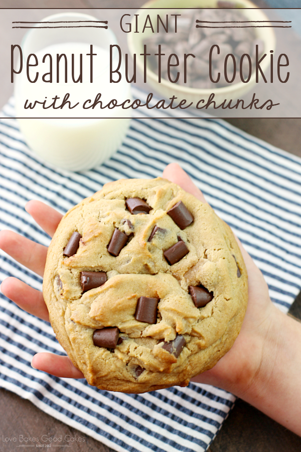 Giant Peanut Butter Cookie with Chocolate Chunks in someones hand. with a glass of milk.