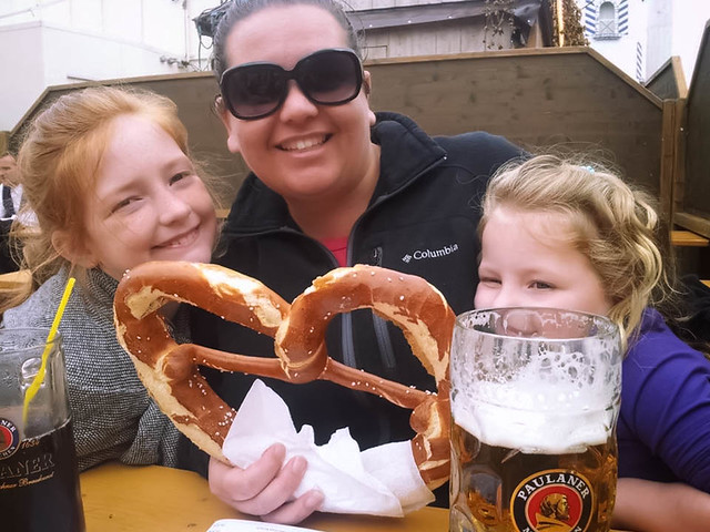 family and children at Oktoberfest enjoying a pretzel