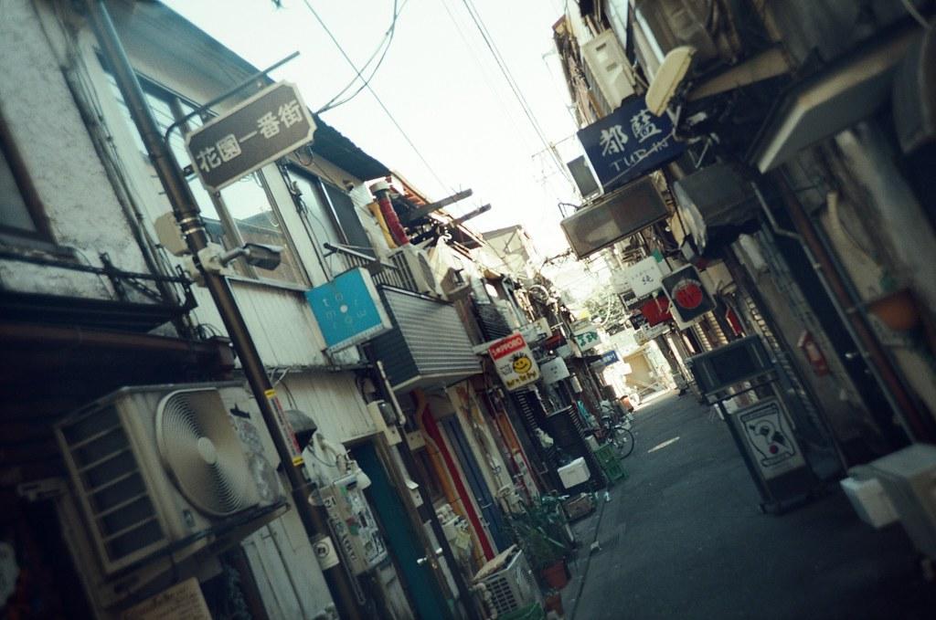 新宿花園一番街 Shinjuku, Japan / KODAK 500T 5219 / Lomo LC-A+ 2016/02/07 新宿花園一番街,上次是晚上來的,這裡很多小間的酒吧,要晚上九點以後店家才會陸續的營業。這次剛好來到新宿,所以過來看看白天沒有營業會是怎樣的景象。  那時候太陽快升到正上方,又剛好天氣很好,所以陽光很強烈的打出像是 spotlight 在街道上。  回來看照片,有點不像日本!  Lomo LC-A+ KODAK 500T 5219 V3 1118-0016 Photo by Toomore