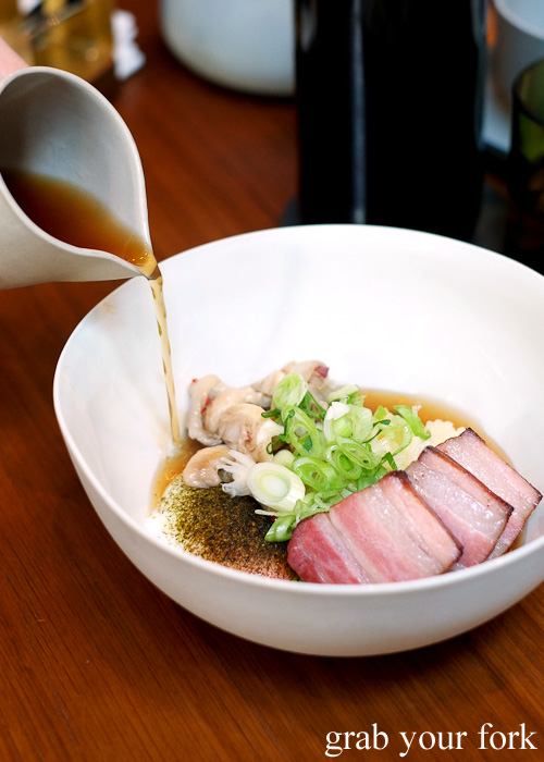 Pouring bacon dashi over breakfast rice with slow cooked hens egg at Kensington Street Social in Chippendale