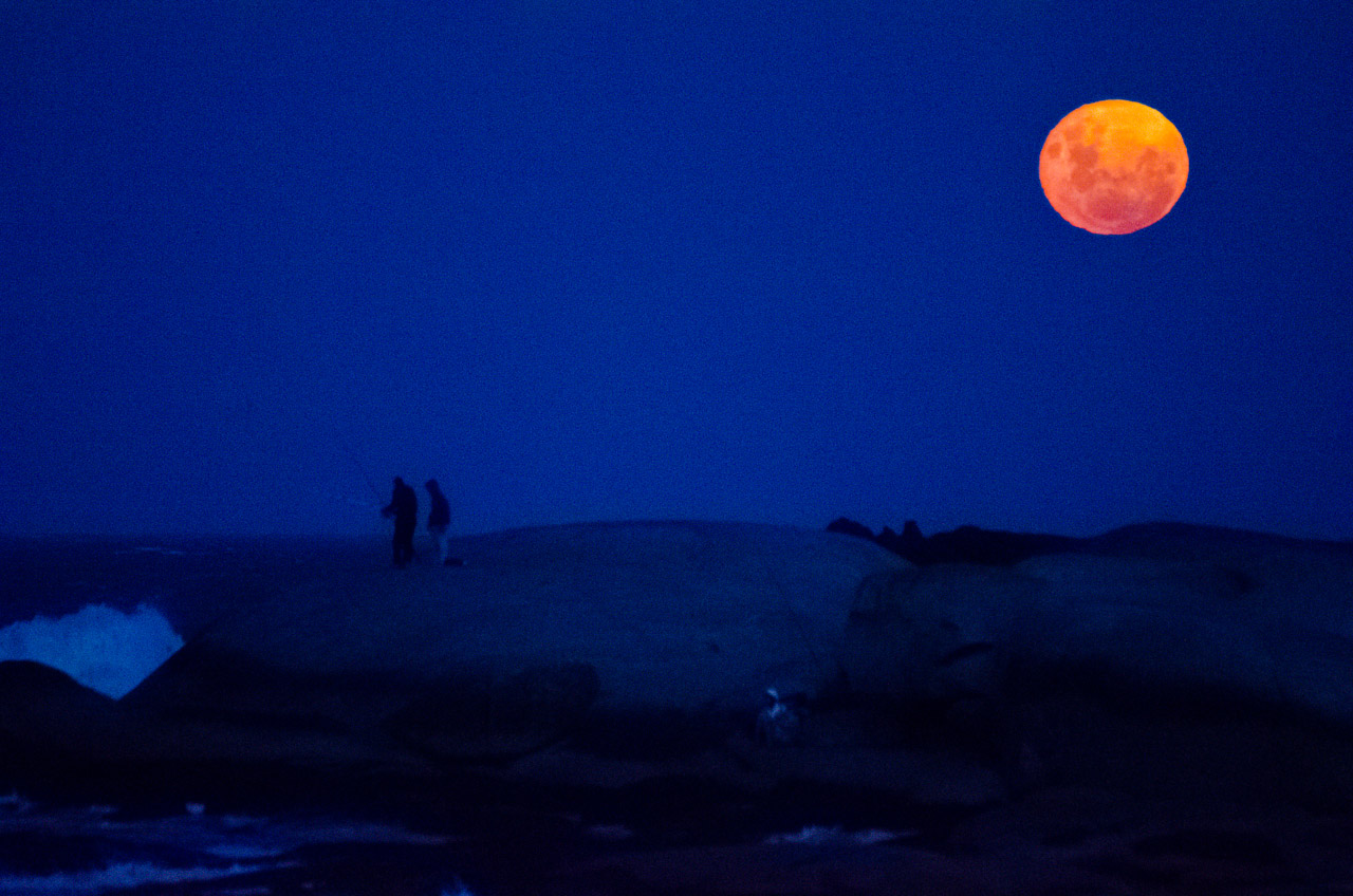 La luna llena sale en el horizonte al caer la noche en Punta del Diablo, mientras que turistas y otros habitantes del lugar continúan pescando. (Elton Núñez)