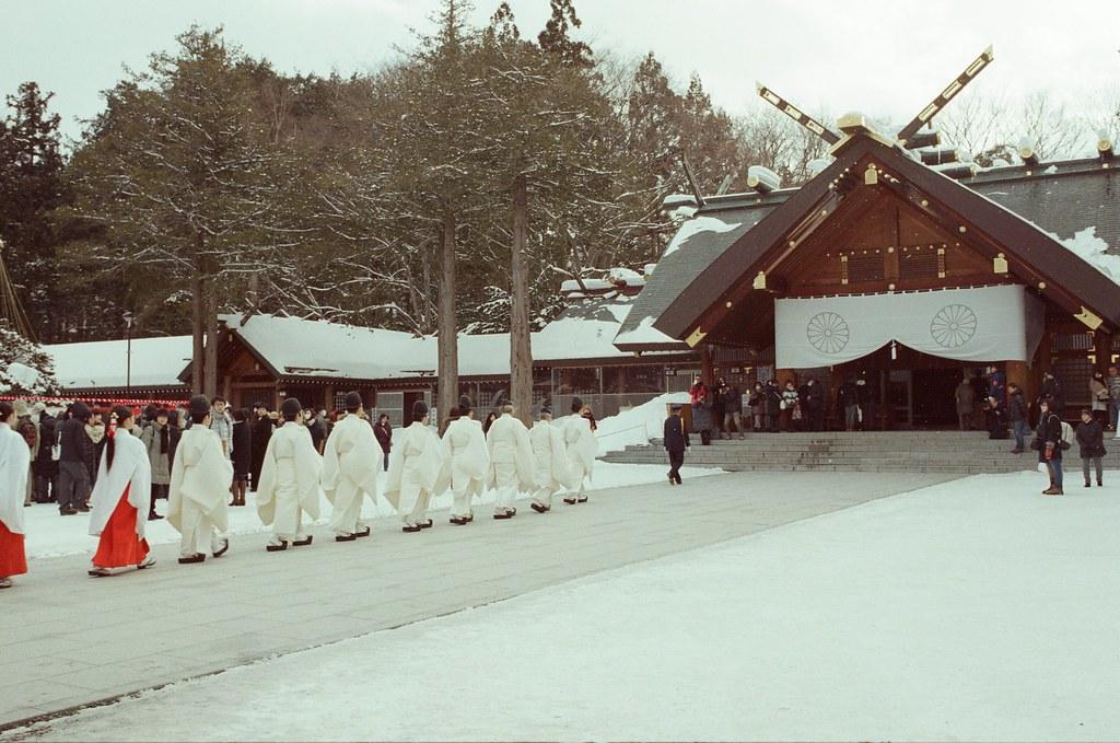 北海道神宮節分祭 Hokkaido, Japan / Fujifilm 500D 8592 / Nikon FM2 2016/02/04 北海道神宮節分祭,有對妖怪丟納豆的儀式,第一次搞懂原來丟納豆的祭典是怎樣的一回事,很新鮮。  那時候天空又飄起雪來,有點冷,站在那裡等很久,附近的居民慢慢聚集在舞台前,等到開始丟祈福的納豆時,大家都往前擠,有點恐怖!  不過真的還滿好玩的,這是這趟旅行第二次來到北海道神宮。  後來回到札幌車站附近的郵便局買明信片,看到電視在轉播各地的節分祭活動,稍微停下來看一下新聞,看看有沒有拍到我!  Nikon FM2 Nikon AI AF Nikkor 35mm F/2D Fujifilm 500D 8592 1114-0005 Photo by Toomore